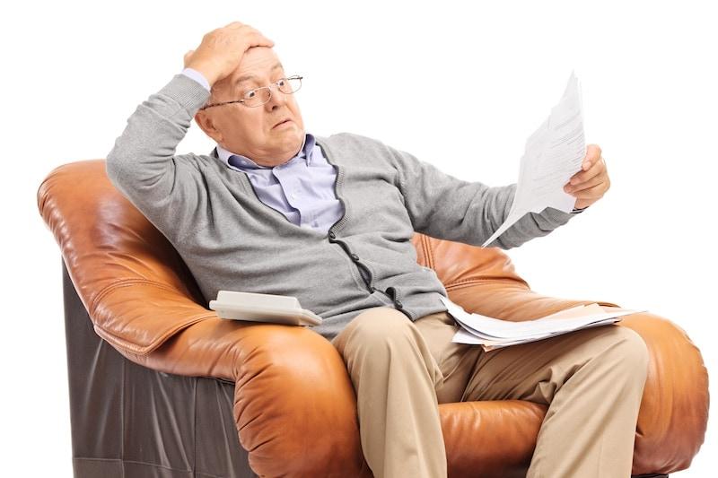 Shocked senior man looking at his bills in disbelief
