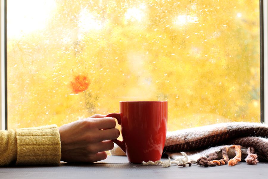 red mug of hot drink, when behind a window is rain in autumn in Boise
