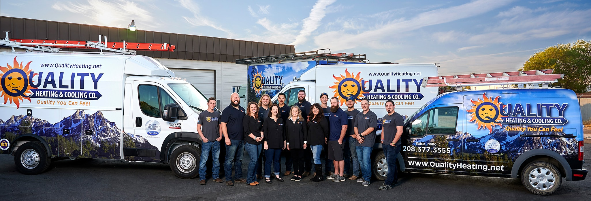The Quality Heating & Cooling team, standing in front of their three service vans outside.