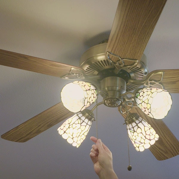 Hand turning on a ceiling fan.
