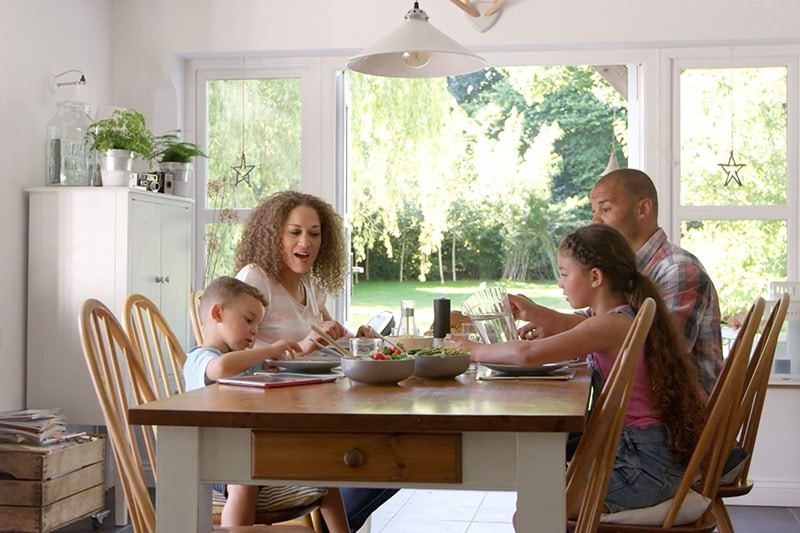 Family eating lunch together at the kitchen table.