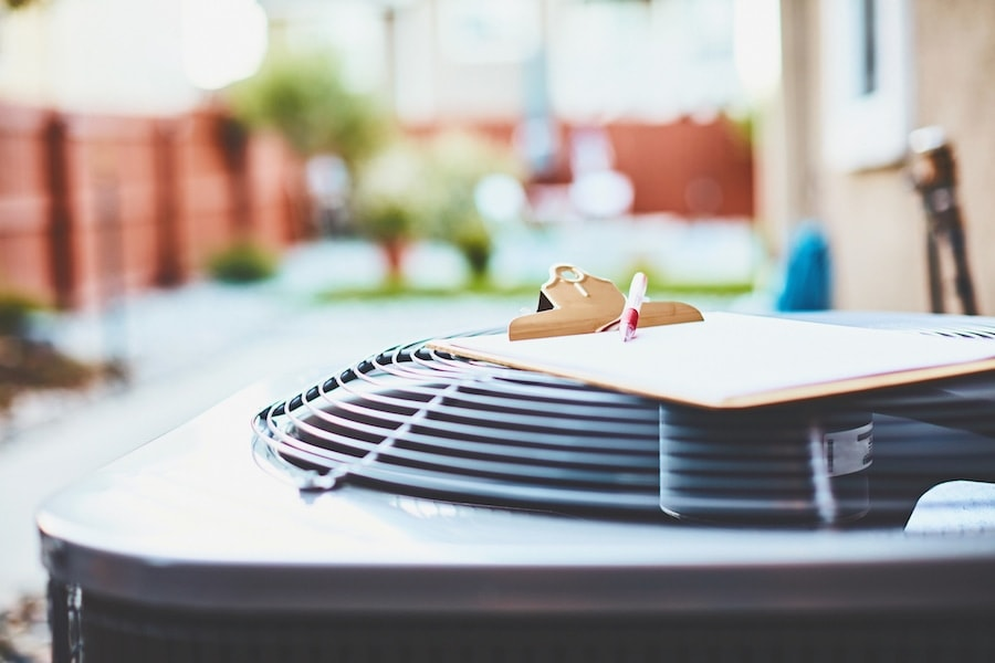 When do I need to replace my air conditioner? Air conditioner with clipboard and paper.