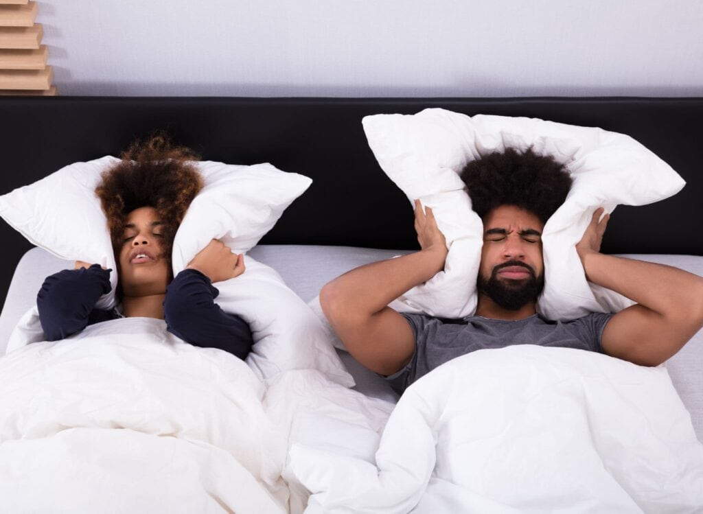 Young Couple Covering Their Ears With Pillow Because Their Furnace is Making Loud Sounds.