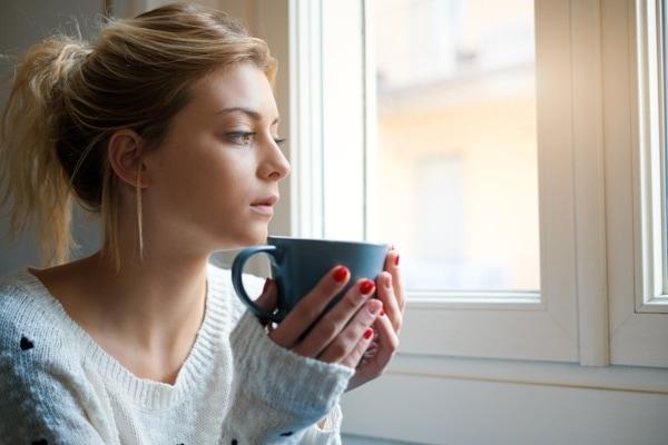 woman with coffee mug near window